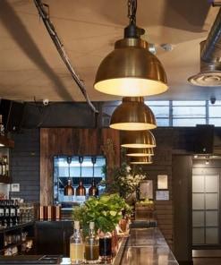 Žalvarinis gaubto formos lubinis pakabinamas šviestuvas BROOKLYN baro erdvėje