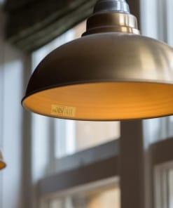 Žalvario spalvos lubinis pakabinamas šviestuvas OLD FACTORY kavinėje