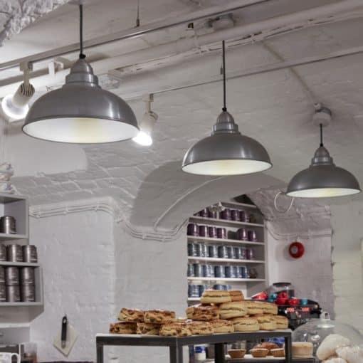 Šviesaus alavo spalvos lubinis pakabinamas šviestuvas OLD FACTORY parduotuvėje