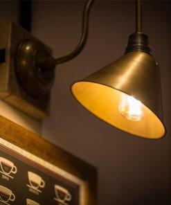 Žalvario spalvos kūgio formos sieninis šviestuvas SWAN NECK interjere